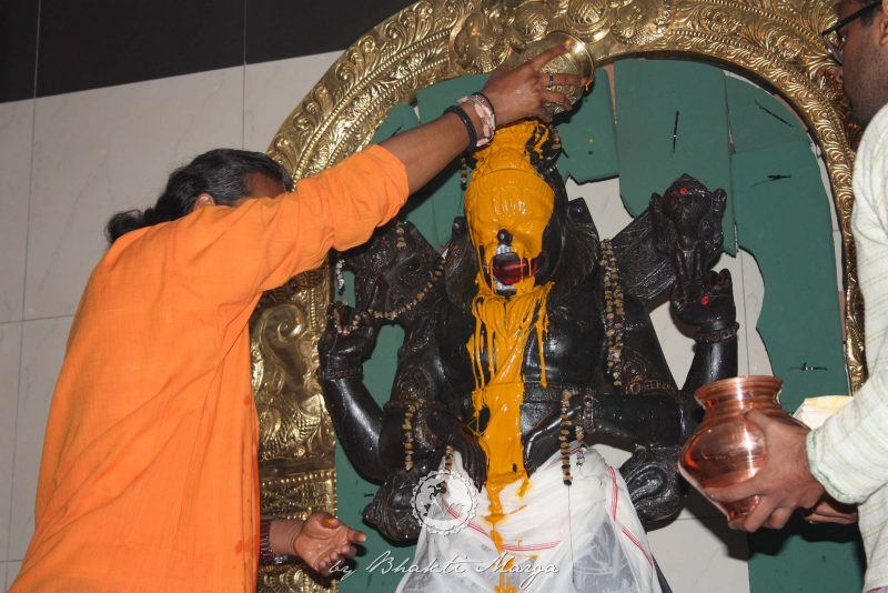 Chandan being poured over Deity during Abhishekam